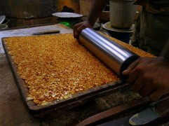 A rolling pin is used to flatten out the peanut mixture before it is cut in cubes